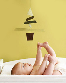Baby laying on changing table looking up at hanging paper christmas tree