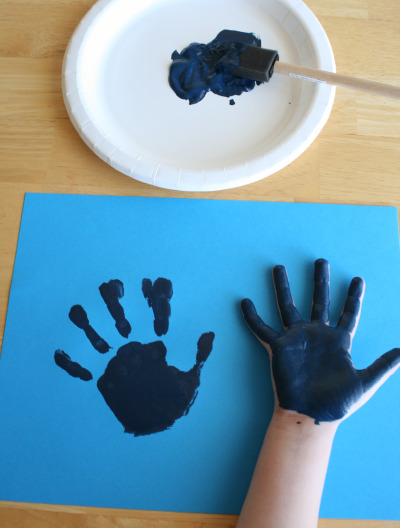 Child's hand print on blue paper