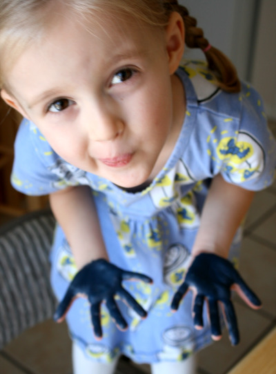 Child with paint on her hands making Menorah craft