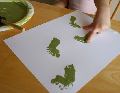 child making green footprint craft