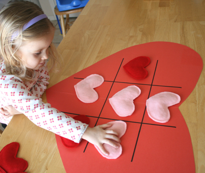 child playing heart tic tac toe game