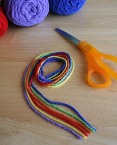 rainbow colored yarn and a pair of scissors on a table