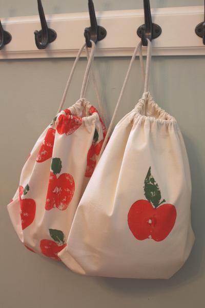 Two apple print backpacks hanging on hooks