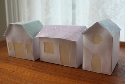Three paper glitter houses on a table