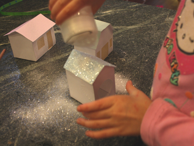 Girl shaking glitter onto small paper house