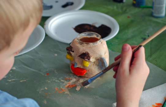 a child painting salt dough covered jar