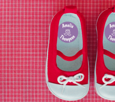 A pair of red baby shoes with a personalized name label on the inside