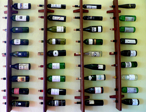 4 racks of wine hanging sideways on a wall