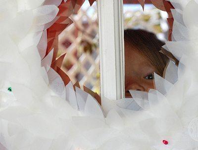 Child peeking through middle of a milk carton holiday wreath