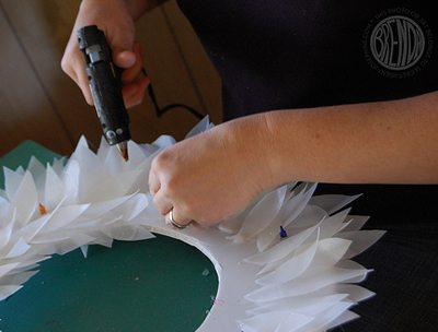 Gluing pieces of milk carton together to make holiday wreath