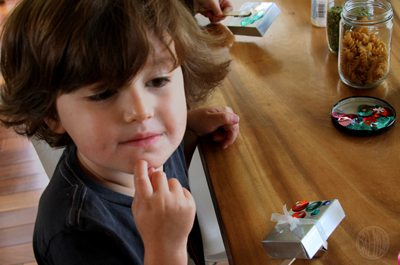 Child at table making a noise maker craft