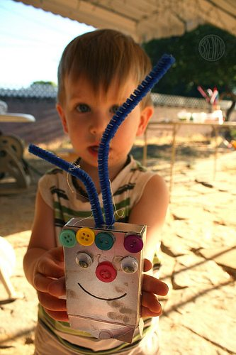 A young boy showing off his recycled creation, a robot made from a juice box and decorated with buttons, pipe cleaner and googly eyes