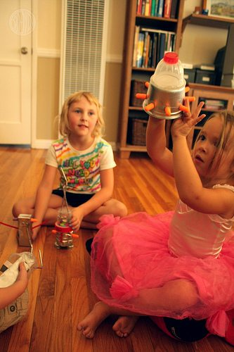 two girls playing with their recycled crafts made from recyclable lunch box items