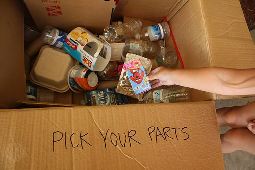 """pick your parts"" written with marker on the flap of a cardboard box filled with recyclable lunch box items"