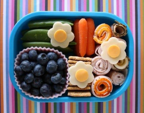 Bento box filled and arranged beautifully with fruits, veggies, meat and cheese