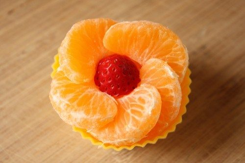 tangerine slices shaped like a flower with a strawberry in the middle