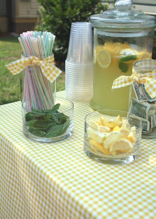 Lemonade stand table with cups, straws, lemon wedges, cups
