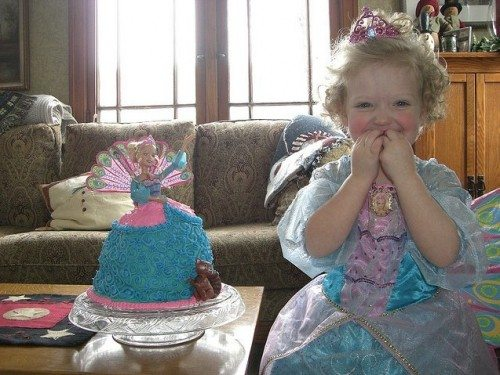 Smiling little girl next to a birthday cake