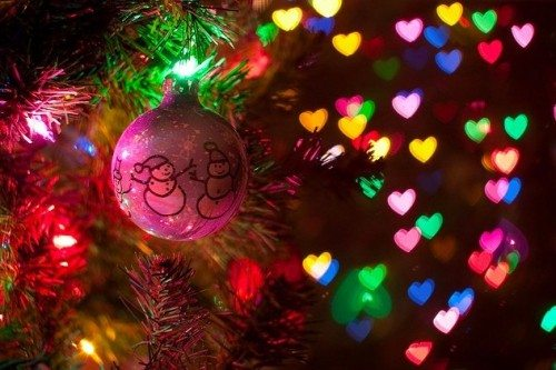 Pink Christmas ornament hanging on tree with lights