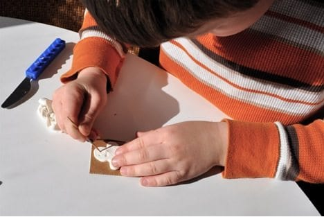 child making homemade holiday stamps out of clay