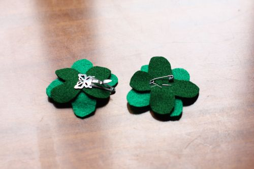 two felt four-leaf clover accessories on a table