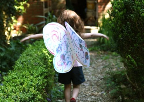 A child wearing paper butterfly wings