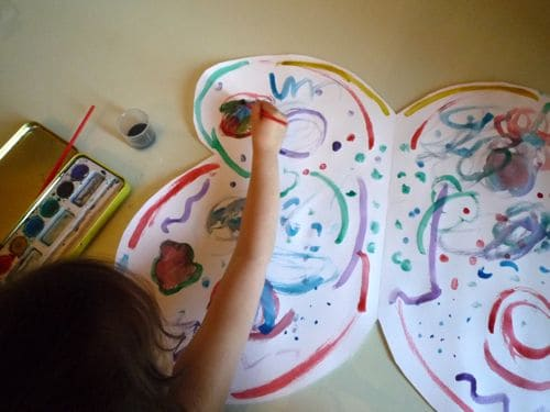 a child painting paper butterfly wings