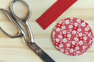 Pair of scissors laying on a table next to a strip of red felt and a circle shaped piece of floral fabric