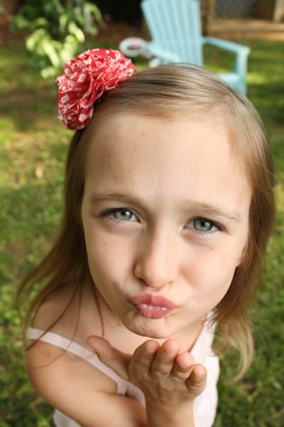 a little girl blowing a kiss, wearing a floral fabric hair clip