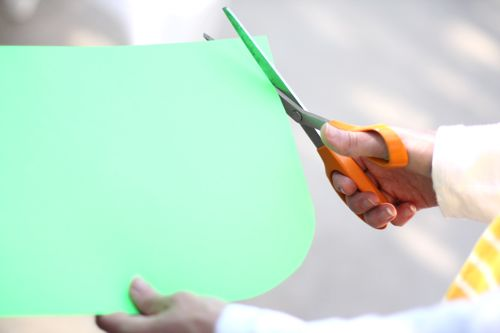 A hand holding scissors cutting a green piece of construction paper
