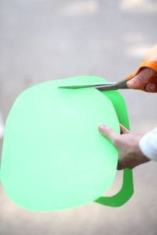 someone cutting a piece of green construction paper with a pair of scissors