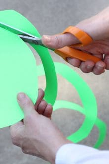 someone using a pair of scissors to cut green construction paper