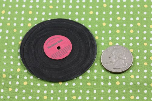 Tiny vinyl made of shrinky dink with a quarter for scale