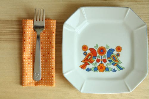 A fork on top of an orange folded fabric napkin next to a white plate