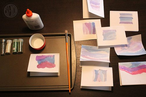 painted cards with glitter and glue laying on top of table
