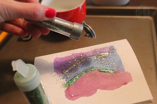 sprinkling glitter on to line of glue