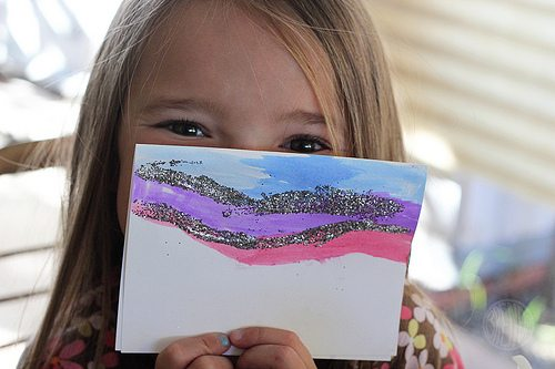 Child holding painted and glittery card