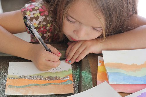 Child writing on painted cards