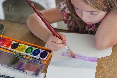 Child painting with watercolor paint