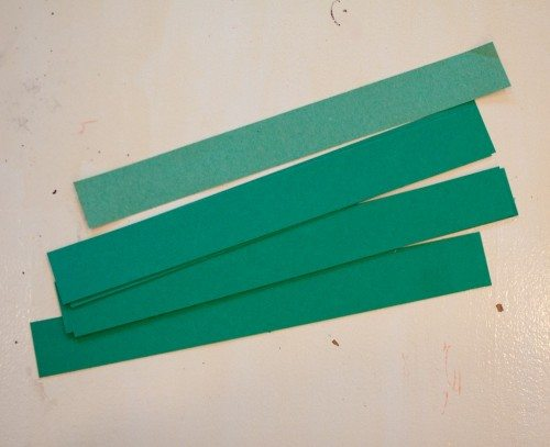Green strips of paper for Christmas tree sun catcher craft
