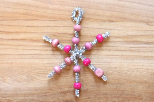 Pink and silver beaded snowflake ornament on a table