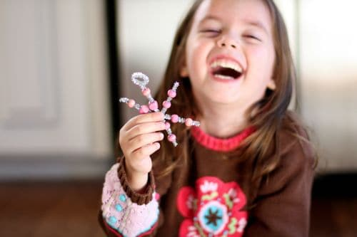 Child laughing holding beaded pipe cleaner ornament craft