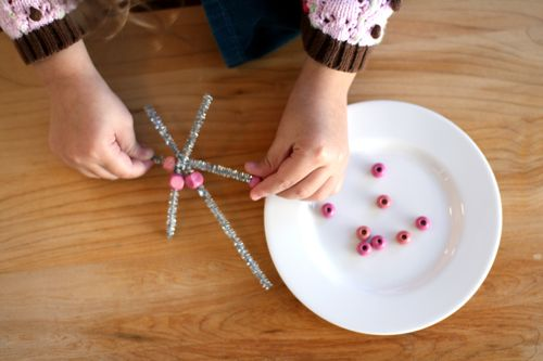 Child adding beads to pipe cleaner