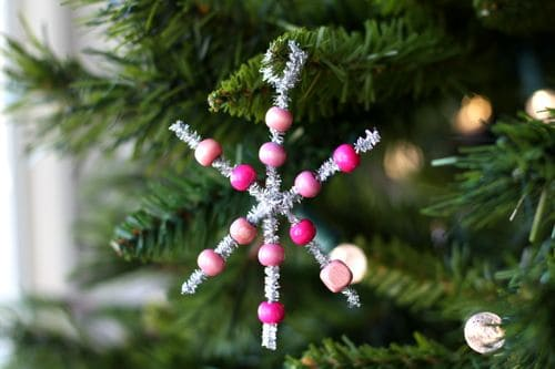 Beaded snowflake ornament hanging on a Christmas tree