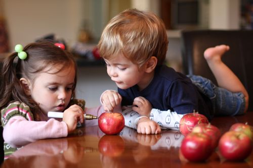 Kids painting apples for holiday decorations