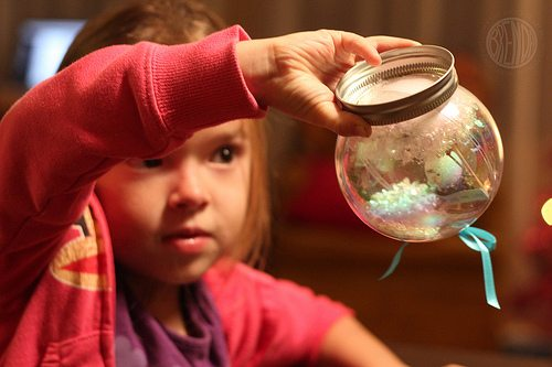 Child holding upside down waterless snow globe