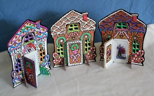Three Gingerbread house photo display crafts sitting on a table