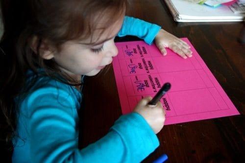 Child signing name on printable valentine