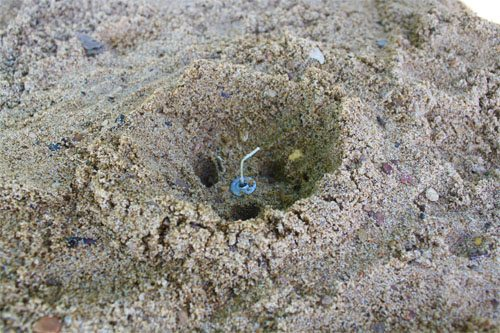 Candle wick in the center of a sand well