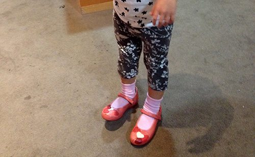 Toddler wearing pink socks and red shoes